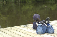 Little boy fishing. Boy fishing from dock and watching his bobber Royalty Free Stock Images