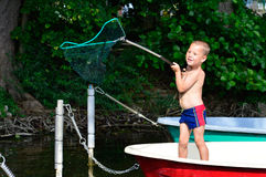 Little boy in fishing boat Stock Photos