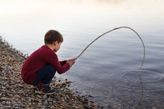 Little boy fishing with branch Stock Photos
