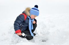 Little boy fishing on the frozen river in winter Royalty Free Stock Photography
