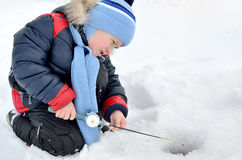 Little boy fishing on the frozen river in winter Royalty Free Stock Images