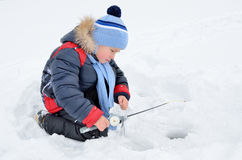 Little boy fishing on the frozen river in winter Stock Photo