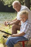 Little Boy Fishing With Grandfather Stock Image