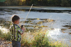 Little boy fishing at lake Stock Images