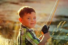Little boy fishing at lake 2. Little boy fishing by a lake on an autumn day at sunset Stock Photography