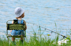 Little boy with fishing rod. Little boy with fishng rod sitting near the lake Stock Image