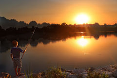 Little boy fishing at sunset. At a beautiful quiet lake Royalty Free Stock Photo
