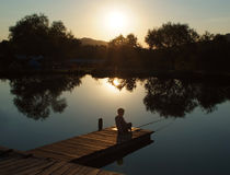 Little boy fishing at sunset pond Royalty Free Stock Photography