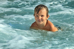 Little boy of five bathing in the sea on a sunny day. Is happy and playing in the water. Child wet with water. The kid is happy and laughing with teeth. The Stock Photos