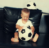 Little boy flaying with football. On a black leather couch Royalty Free Stock Image