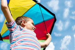 Little boy flies a kite into the blue sky. Boy with bright kite over the head on the blue sky view Royalty Free Stock Photo
