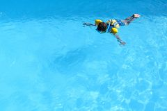 Little boy floating in the corner of the swimming pool. With some aids and schnorkel stock images