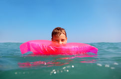 Little boy floating in sea on matress Royalty Free Stock Photos