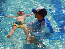 Little boy floating with swim instructor. During a swimming lesson in a pool royalty free stock photography