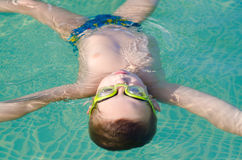 Little boy floating on the water surface of the swimming pool Royalty Free Stock Image