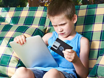 Little boy with floppy disk and tablet pc Stock Photography