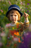 Little boy in a flowers field at sunset Royalty Free Stock Images