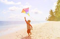 Little boy flying a kite on tropical beach Stock Photos