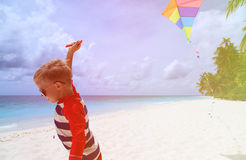 Little boy flying a kite on tropical beach Stock Image