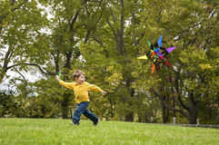 Young child flying a kite. Little boy in a yellow shirt running and flying a colorful kite Royalty Free Stock Image