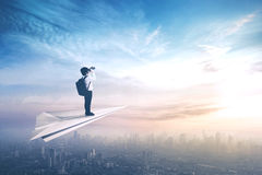 Little boy flying on paper aeroplane. Picture of a little boy standing on a paper aeroplane while flying above a city and looking through a binoculars Royalty Free Stock Photo