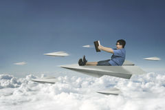 Little boy flying with paper plane. Picture of a little boy flying with a paper plane on the sky while holding a book Stock Image
