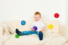 The little boy and flying  spheres. The little boy and flying multi-colored spheres Royalty Free Stock Images