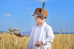 Little boy flying a toy plane in a wheat field Royalty Free Stock Image