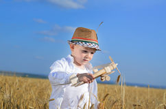 Little boy flying a toy plane in a wheat field Royalty Free Stock Photography