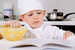 Little boy following a recipe as he bakes a cake Royalty Free Stock Photos