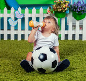 Little boy with football drinking milk Royalty Free Stock Images