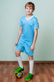 Little boy in football uniform standing, one leg on a ball Stock Photography