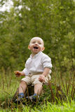 Little boy in the forest. Little smiling boy in white shirt in the woods Royalty Free Stock Photography
