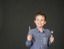 Little boy with fork and knife. Hungry child.