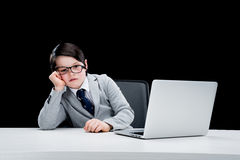 Little boy in formal suit and eyeglasses working with laptop. Tired little boy in formal suit and eyeglasses working with laptop Royalty Free Stock Photo