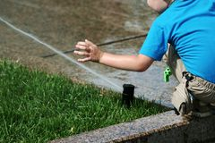 Little boy and fountain. The little boy playing with an irrigating fountain Royalty Free Stock Images
