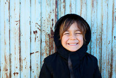 Little boy in front of a blue metal door Stock Photography