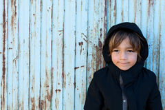Little boy in front of a blue metal door Royalty Free Stock Image