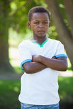 Little boy frowning at camera with arms crossed in the park Stock Photos