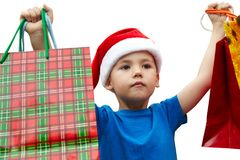 Little boy in fur-cap with shopping bags. Christmas. Little boy in fur-cap with shopping bags. Isolated over white background. Christmas Stock Photo