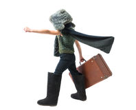 Little boy in a fur hat and felt boots purposefully moving forward with developing scarf and holds old suitcase in his hand Royalty Free Stock Image