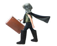 Little boy in a fur hat and felt boots purposefully moving forward with developing scarf and holds old suitcase in his hand Royalty Free Stock Photo