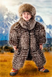 A little boy in a fur hat and fur vest in the steppe.Small tribal leader.Lord of the steppe. Small tribal leader.Lord of the steppe.A little boy in a fur hat stock photo