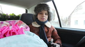 Little boy in a fur hat and a newborn baby ride in the car. stock footage