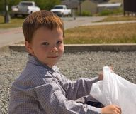 Little Boy with Garbage Bag Outside. This 5 year old Caucasian boy is sitting outside with a white garbage bag picking up litter in his neighborhood community Stock Image