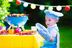 Little boy at garden grill party. Children grilling meat. Family camping and enjoying BBQ. Little boy at barbecue preparing steaks, kebab and corn. Kids eating Royalty Free Stock Photography