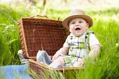 Little boy in the garden. Playing with picnic basket. Stock Photos