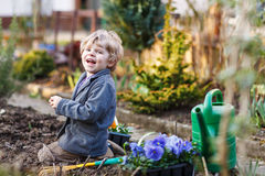 Little boy gardening and planting flowers in garden Stock Photo