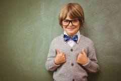 Little boy gesturing thumbs up against blackboard. Portrait of cute little boy gesturing thumbs up against blackboard in the classroom Royalty Free Stock Images