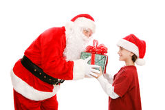 Little Boy Gets Gift From Santa. Cute little boy getting a Christmas gift from Santa Claus. Isolated on white royalty free stock photos